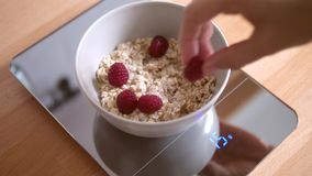 Woman Making Smile Face with Raspberries in Oatmeal Bowl on Food Scale. Healthy Breakfast for Children. 4K.