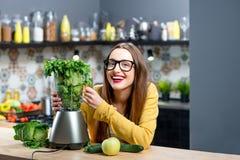 Woman making smoothie Stock Image