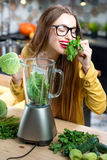 Woman making smoothie Stock Images