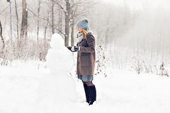 Woman making a snowman in winter time Royalty Free Stock Images