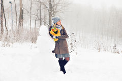 Woman making a snowman in winter time Royalty Free Stock Photography