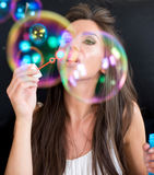 Woman making soap bubbles Royalty Free Stock Images