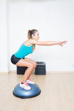 Woman making squats on balance trainer royalty free stock images