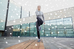 Woman making step exercise on city street bench. Fitness, sport, training, people and healthy lifestyle concept - young woman making step exercise on city street Royalty Free Stock Photo