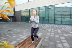 Woman making step exercise on city street bench. Fitness, sport, training, people and lifestyle concept - young woman making step exercise on city street bench Stock Image