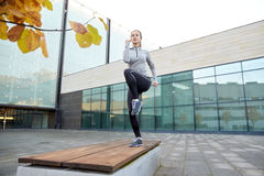 Woman making step exercise on city street bench. Fitness, sport, training, people and lifestyle concept - young woman making step exercise on city street bench Stock Photography