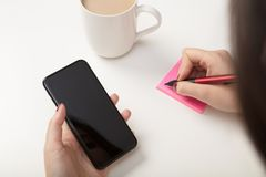 Woman making a sticky note reminder. As she copies something off her mobile phone in an over the shoulder view to the blank screen Royalty Free Stock Photos
