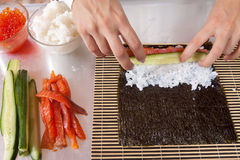 Woman making   sushi rolls Royalty Free Stock Images