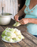 Woman making tamales in Cuba. The tamal  is a traditional Mesoamerican dish made of masa (a starchy dough, usually corn-based), which is steamed or boiled in a Royalty Free Stock Images