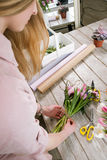 Woman making tulip bouquet top view. Unrecognizable florist make floristry assemble in workshop on wooden background Stock Photo