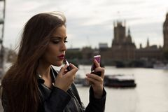Woman making up with bigben and parlament in background Royalty Free Stock Photos