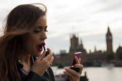 Woman making up with bigben and parlament in background Royalty Free Stock Photography