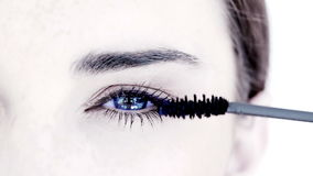 Woman making up her eye with mascara Royalty Free Stock Photography