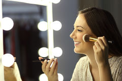 Woman making up using a brush. Profile of a woman making up using a brush in front of a make up mirror Stock Photo