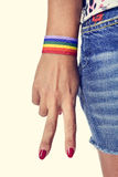 Woman making the V sign, with a bracelet patterned as the rainbo Royalty Free Stock Images