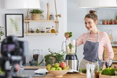 Woman making video for a blog. Pretty young woman making video for her blog about food Stock Image