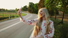 Woman making video call near countryside road. Young lady smiling and using modern smartphone to make video call while hitchhiking in Europe countryside stock video footage