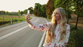 Woman making video call near countryside road. Young lady smiling and using modern smartphone to make video call while. Hitchhiking in Europe countryside. 4K stock video