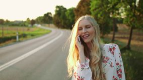 Woman making video call near countryside road. Young lady smiling and using modern smartphone to make video call while hitchhiking in Europe countryside stock footage