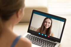 Woman making video call to female friend on laptop. Girlfriends having chat via video call application on computer. Long distance friendship, virtual Stock Photography