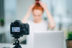 Woman making a video for her blog on hairstyle using camera. Woman making a video for her blog on hairstyle using a tripod mounted digital camera. Young female royalty free stock image