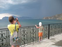 Woman making video of thunderstorm on sea Royalty Free Stock Images