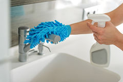 Woman making water tap clean. Housewife using special blue glove and detersive for cleaning crane in kitchen. Close up of female hands Stock Photos