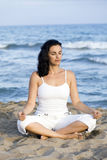 Woman making yoga on the beach stock photo