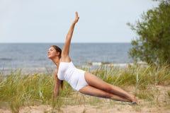 Woman making yoga at the beach Royalty Free Stock Photos