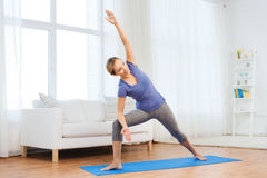Woman making yoga bikram triangle pose on mat. Fitness, sport, people and healthy lifestyle concept - woman making yoga bikram triangle pose on mat Stock Images