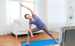 Woman making yoga bikram triangle pose on mat. Fitness, sport, people and healthy lifestyle concept - woman making yoga bikram triangle pose on mat Stock Photography