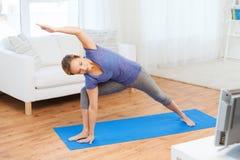Woman making yoga bikram triangle pose on mat Stock Image