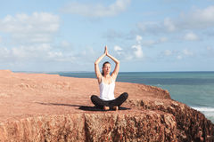 Woman making yoga on cliffs Stock Photography