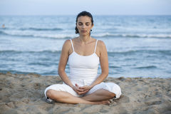 Woman making yoga exercise on the beach Royalty Free Stock Images