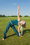 Woman making Yoga exercises in top of a stone wall Royalty Free Stock Image
