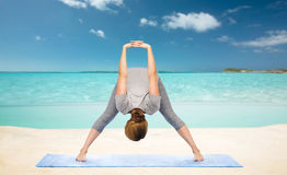 Woman making yoga  forward bend on beach Royalty Free Stock Photography