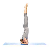 Woman making yoga in headstand pose on mat Royalty Free Stock Photos