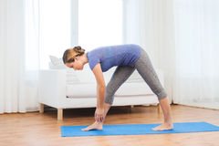 Woman making yoga intense stretch pose on mat Stock Photos