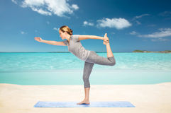 Woman making yoga in lord of the dance pose Royalty Free Stock Image