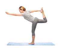 Woman making yoga in lord of the dance pose on mat Royalty Free Stock Photography