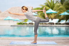 Woman making yoga in lord of the dance pose on mat Royalty Free Stock Image