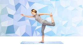 Woman making yoga in lord of the dance pose on mat Royalty Free Stock Photo