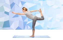 Woman making yoga in lord of the dance pose on mat Stock Photo
