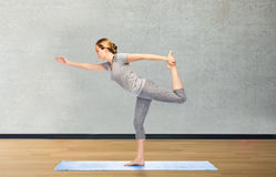 Woman making yoga in lord of the dance pose on mat Stock Photos
