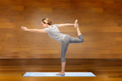 Woman making yoga in lord of the dance pose on mat Royalty Free Stock Images