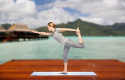 Woman making yoga lord of the dance pose outdoor. Fitness, sport, people and healthy lifestyle concept - woman making yoga in lord of the dance pose on wooden Stock Photo