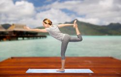 Woman making yoga lord of the dance pose outdoors. Fitness, sport, people and healthy lifestyle concept - woman making yoga in lord of the dance pose on wooden Stock Photography