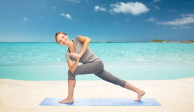 Woman making yoga low angle lunge pose on mat Stock Images