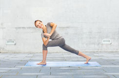Woman making yoga low angle lunge pose on mat. Fitness, sport, people and healthy lifestyle concept - woman making yoga low angle lunge pose on mat over urban royalty free stock image