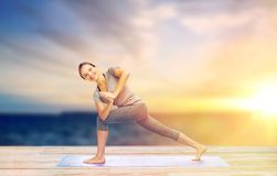 Woman making yoga low angle lunge pose on mat. Fitness, sport, people and healthy lifestyle concept - woman making yoga low angle lunge pose on pier over sea royalty free stock images